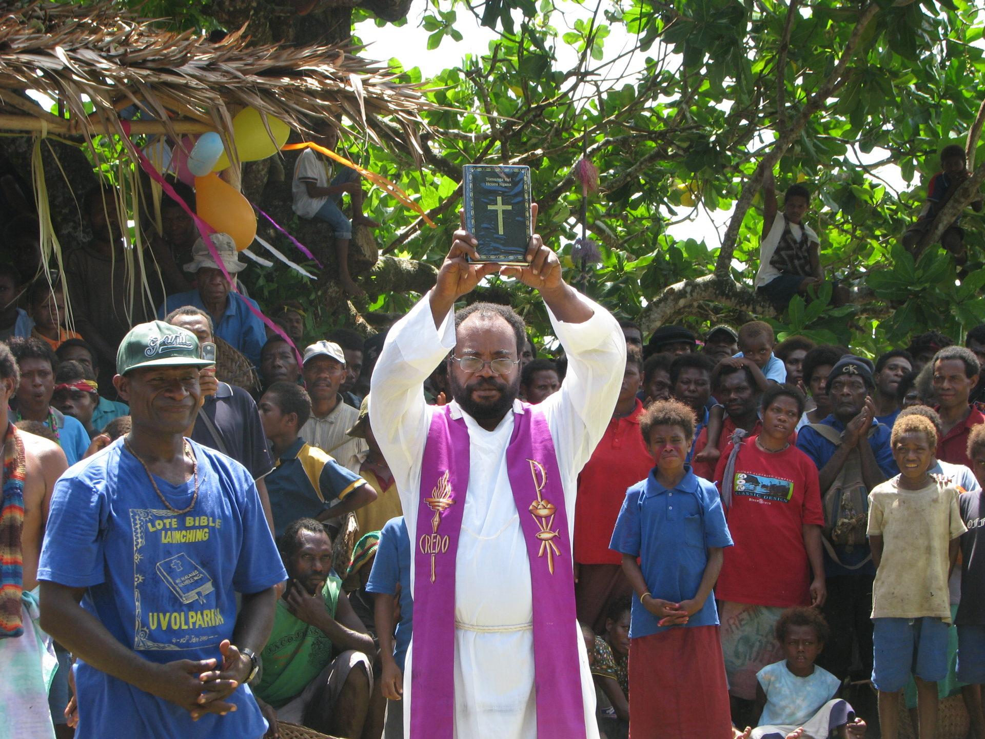 新約聖書を掲げる司祭