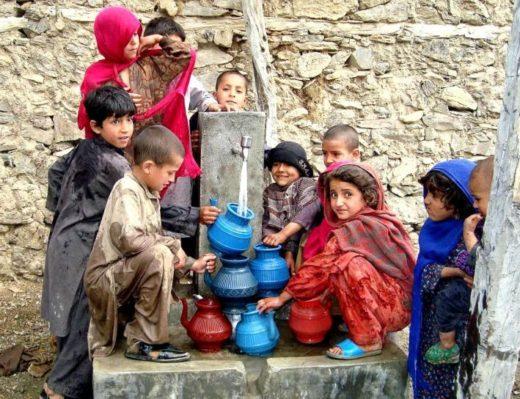 アフガニスタンで綺麗な水を容器に入れる子どもたち